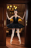 Ballerina in black tutu standing on pointes in doorway