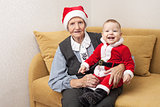 Christmas funny small baby in Santa Claus clothes with his grandmother