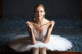 Ballerina holding pearl necklace and smiling