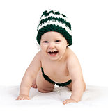Happy baby boy in knitted hat crawling over white