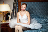Professional ballet dancer sitting on sofa and looking down in luxury interior