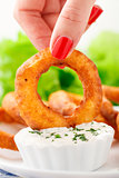 Fingers holding onion ring