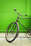 Old bicycle leaning on green wall