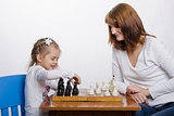 Mother teaches daughter to play chess