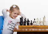 Girl playing chess in a good mood