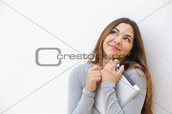 Candid  innocent teenager girl cuddling a tablet and looking above