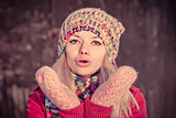 Young Woman Beautiful Winter time wearing knitted hat and gloves and blowing air kiss Lifestyle Expression emotions concept and Christmas holiday