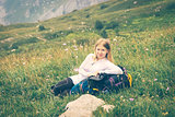 Woman traveler relaxing outdoor on green valley with backpack enjoying nature Hiking traveling film effect colors
