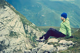 Woman Hiker in Mountains relaxing on rocky cliff outdoor traveling hiking
