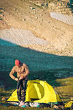 Man Traveler with Tent Camping arranging hiking equipment in Mountains Traveling concept