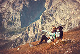 Woman Traveler with Backpack relaxing in Mountains with rocks on background mountaineering hiking sport lifestyle concept