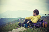 Man Traveler with backpack relaxing with Mountains on Background Summer Traveling Outdoor