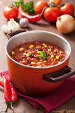 mexican chili con carne in red rustic pot with ingredients