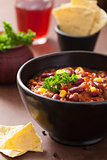 mexican chili con carne in black plate with tortilla