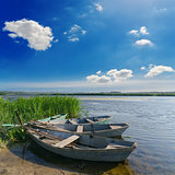beautiful river and old boats near green grass under cloudy sky
