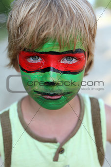 boy child with a painted mask on her face