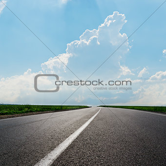asphalt road to horizon under cloudy sky