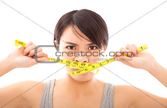 angry woman holding ruler to close mouth