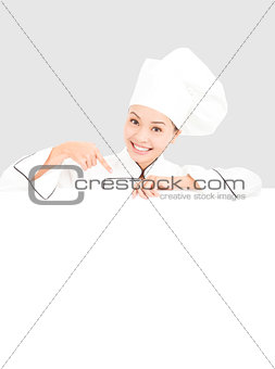 smiling  young woman chef pointing  with blank board