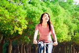 Pretty asian young woman riding bike in the park