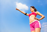 smiling sporty woman watching and pointing far away