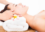 relaxing massage of face for asian woman in spa salon