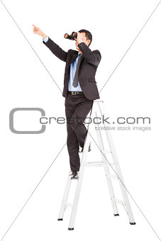 asian businessman using binoculars standing  on stair