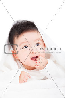 smiling baby sucking  finger under  blanket or towel