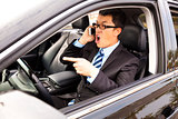 irate businessman talking with cell phone in the car