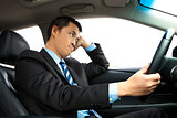 depressed businessman holding head and driving car