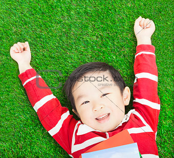 Beauty smiling child boy resting and hand up with books