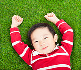 little smiling boy resting and hand up  in meadow