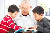 grandfather and grandchildren reading a book