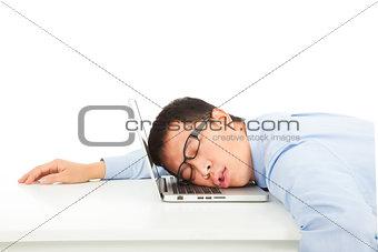 Tired overworked businessman sleeps on laptop