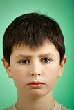studio portrait of young boy on green background