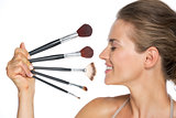 Profile portrait of happy young woman with makeup brushes