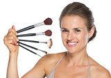 Happy young woman holding makeup brushes