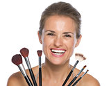 Smiling young woman holding makeup brushes