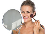 Young woman looking in mirror and makeup