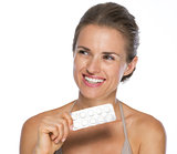 Smiling young woman with blistering package of pills looking on