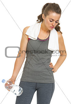 Tired fitness young woman with towel and bottle of water