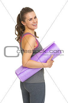 Portrait of happy fitness young woman with fitness mat