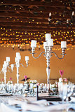Candelabra with candles on decorated wedding reception tables
