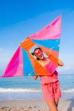 Girl in dress with sunglasses on the sea beach with kite have jo