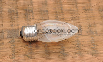 old burned out light bulb on wood background
