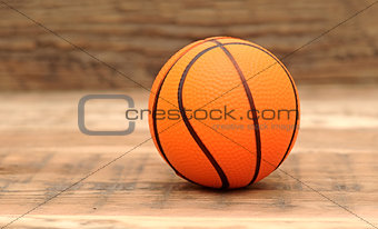 Toy basketball on wood background