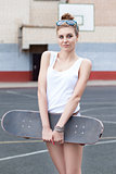 beautiful sexy lady in jeans shorts with skateboard at sport cou