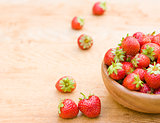 Close-up of strawberries in vintage wooden bowl on wooden table
