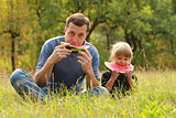 father with a small daughter eat watermelon on the grass