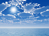 cloudy blue sky and sun above a blue surface of the sea